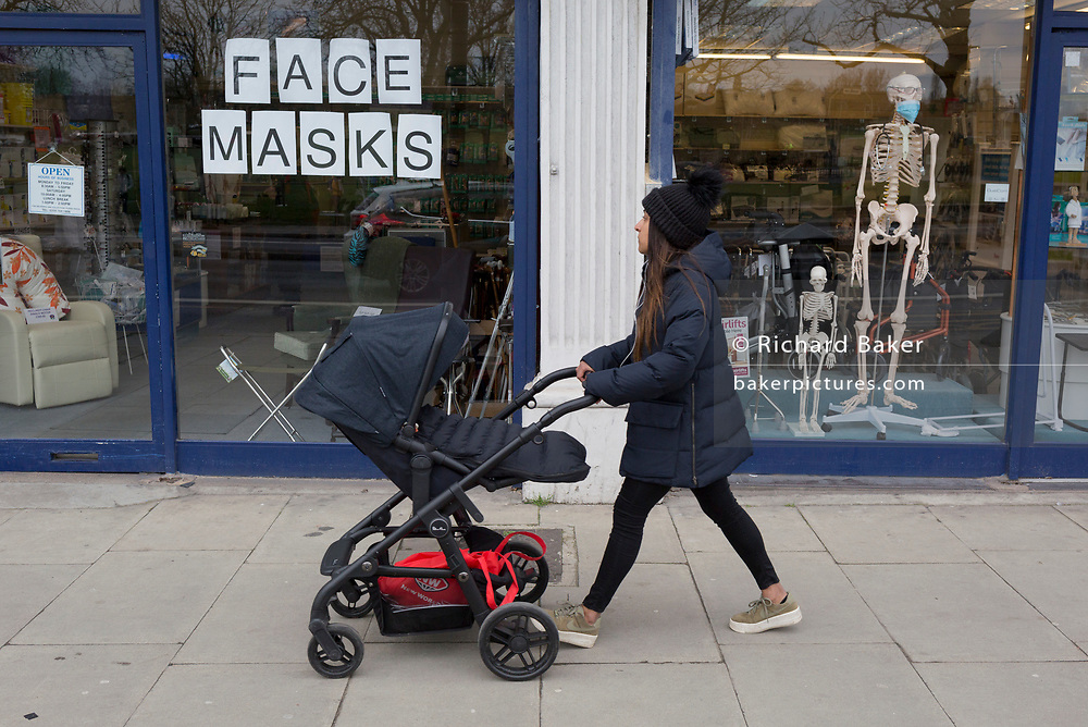 As the Coronovirus pandemic takes hold across the UK, with 53 cases now reported by health authorities, a mother and child walks past the window of a medical equipment business in south London, displays a face masks sign and surgical masks on a skeleton mannequin, on 4th March 2020, in London, England.