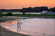 Nederland, Nijmegen, 18-7-2020 Ondergaande zon vanuit de Ooijpolder richting Lent aan de overkant van de rivier de Waal .Een jong stel staat in het water en geniet van de rust . Foto: ANP/ Hollandse Hoogte/ Flip Franssen