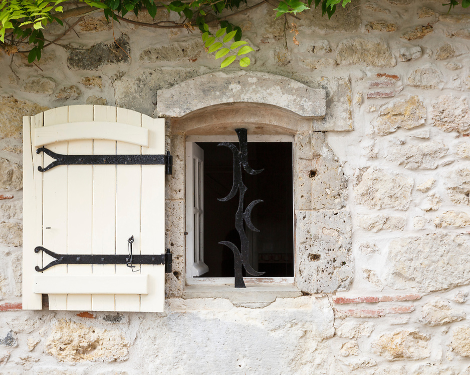 Window and shutter on a traditional French farmhouse in Aquitaine showing the intricate patterns of the limestone