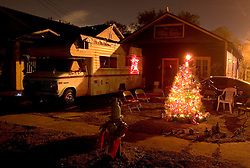 21 December 2005. New Orleans, Louisiana.  Post Katrina aftermath. <br />  A camper van, the new home of Pijer Day sits outside what was once her home in the flood ravaged Mid City neighbourhood. Pijer erected a tree with a miniature village on the corner of the street to cheer the four residents who have returned to the neighbourhood. All lights powered by generator.<br /> Photo; ©Charlie Varley/varleypix.com