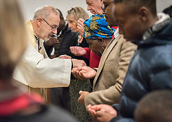 24 November 2019, Geneva, Switzerland: Rev. Michael Rusk distributes bread to World Council of Churches moderator Dr Agnes Abuom, as he presides over Sunday service at the Emmanuel Episcopal Church, Geneva.