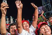 01 MARCH 2013 - BANGKOK, THAILAND: . Pheu Thai supporters cheer for Pongsapat Pongchareon, the Pheu Thai Gubernatorial candidate for Bangkok during the last campaign rally of the race. The election is Sunday, March 3 and no campaigning is allowed 24 hours before election day. Police General Pongsapat Pongcharoen (retired), a former deputy national police chief who also served as secretary-general of the Narcotics Control Board is the Pheu Thai Party candidate in the upcoming Bangkok governor's election. He resigned from the police force to run for Governor. Former Prime Minister Thaksin Shinawatra reportedly personally recruited Pongsapat. Most of Thailand's reputable polls have reported that Pongsapat is leading in the race and likely to defeat Sukhumbhand Paribatra, the Thai Democrats' candidate and incumbent. The loss of Bangkok would be a serious blow to the Democrats, whose national base has been the Bangkok area.    PHOTO BY JACK KURTZ