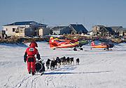 Alaska. Lance Mackey approaching Unalakleet past ski planes parked on the slough, Iditarod 2007.