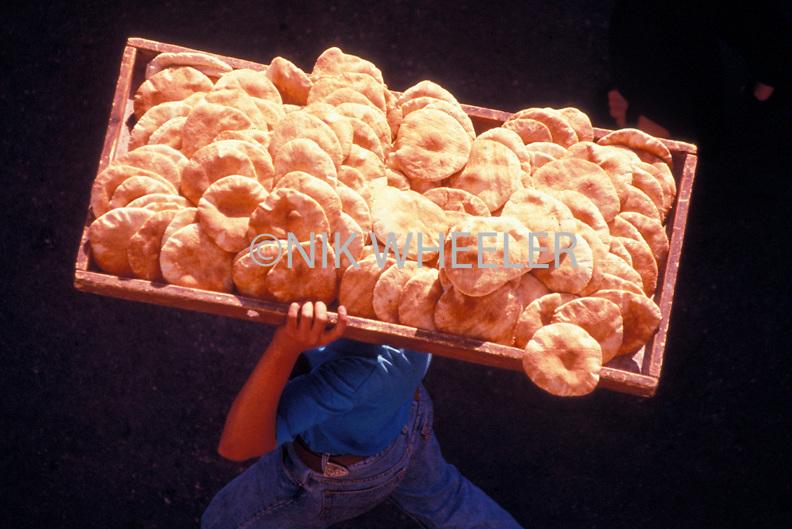 Boy carries tray of pita bread Jerusalem