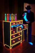 A man with a cowboy hat holds onto a sock while standing next to a chest of drawers with glowing trim.Black light