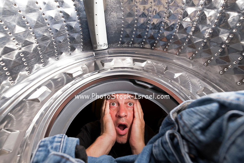 Washing day. shocked man looks at the clothes in the washing machine