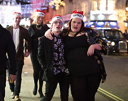 © Licensed to London News Pictures. 20/12/2014. Revellers enjoy a night out in central London to celebrate the start of the Christmas holidays. The last Friday before Christmas is also known as Mad Friday, which is one of the busiest nights of the year with millions descending into bars and pubs for some festive fun. Photo credit : Isabel Infantes / LNP