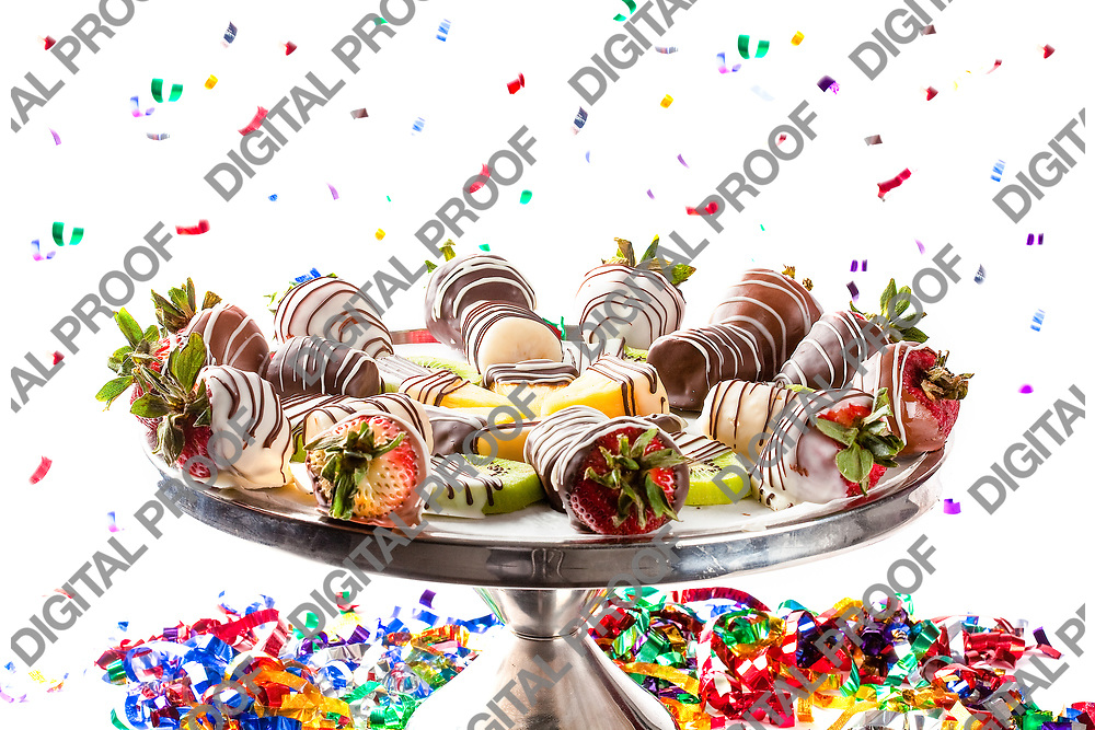 Strawberries and other fruits covered in chocolate on a plate of appetizers for celebration in studio with white background