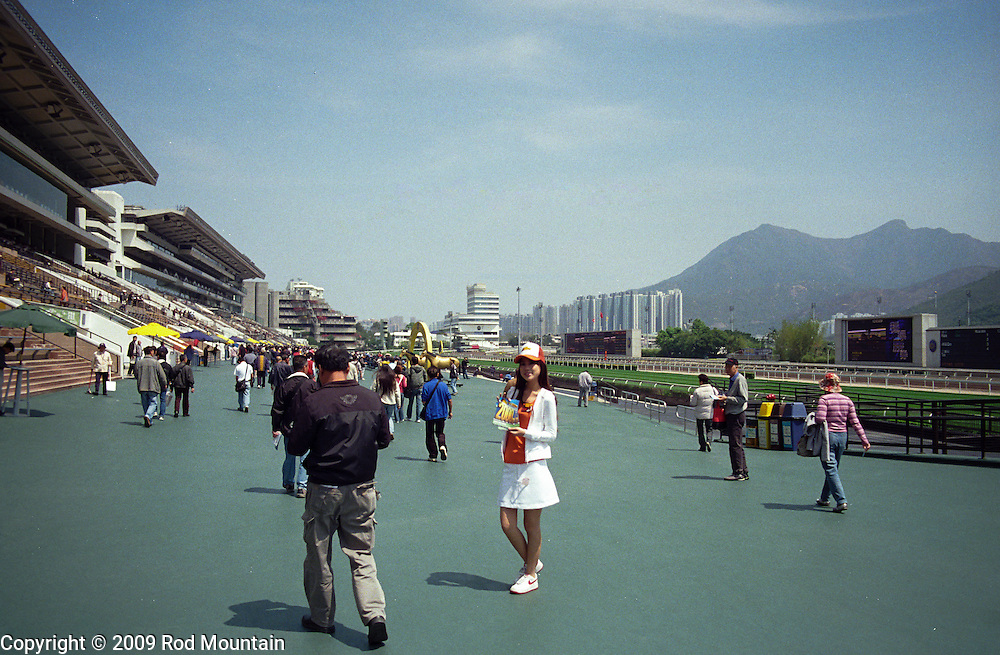 A young girl hands out the day's racing information at the Sha Tin Racecourse in Hong Kong.