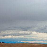 A spring storm hovers over harvested wheat fields in the Gallatin Valley, near Bozeman, Montana.
