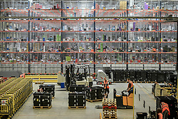 Embargoed to 0001 Friday November 16 Workers move forklifts in front of huge racks containing thousands of items at Amazon's fulfillment centre in Swansea, in the run up to Black Friday.
