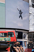 An image of a leaping figure from a Piccadilly Circus Calvin Klein ad whose slogan is 'Dare to Defy', and resting Londoners on 'Freedom Day'. This date is what Prime Minister Boris Johnson's UK government has set as the end of strict Covid pandemic social distancing conditions with the end of mandatory face coverings in shops and public transport, on 19th July 2021, in London, England.