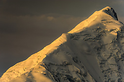 Mount Brooks, a 11,940 foot tall peak in the Alaska Range, is bathed in morning sunlight as seen from the Wonder Lake campground in Denali National Park and Preserve in Alaska. Mount Brooks, first climbed in 1952, is located at the confluence of the Muldrow, Traleika, and Brooks glaciers. The mountain is named after geologist Alfred Hulse Brooks who is credited with determining that the Brooks Range, the biggest mountain range in Arctic Alaska, was separate from the Rocky Mountains.
