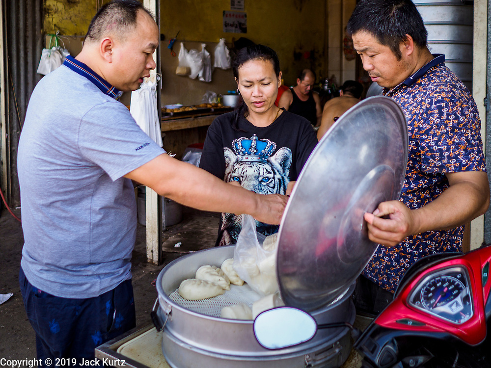 """14 FEBRUARY 2019 - SIHANOUKVILLE, CAMBODIA: A Chinese worker (left) buys steamed buns a Chinese baker (right) who has a shop in the Leu Market in Sihanoukville. The Cambodian woman sells buns to the baker's Cambodian customers. There are thousands of Chinese workers in Sihanoukville who work to support the casino and hotel industry in the town. There are about 80 Chinese casinos and resort hotels open in Sihanoukville and dozens more under construction. The casinos are changing the city, once a sleepy port on Southeast Asia's """"backpacker trail"""" into a booming city. The change is coming with a cost though. Many Cambodian residents of Sihanoukville  have lost their homes to make way for the casinos and the jobs are going to Chinese workers, brought in to build casinos and work in the casinos.      PHOTO BY JACK KURTZ"""
