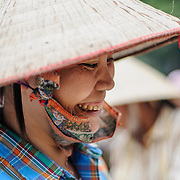 A woman wearing a traditional Vietnamese conical hat at a food market in Hanoi, Vietnam.