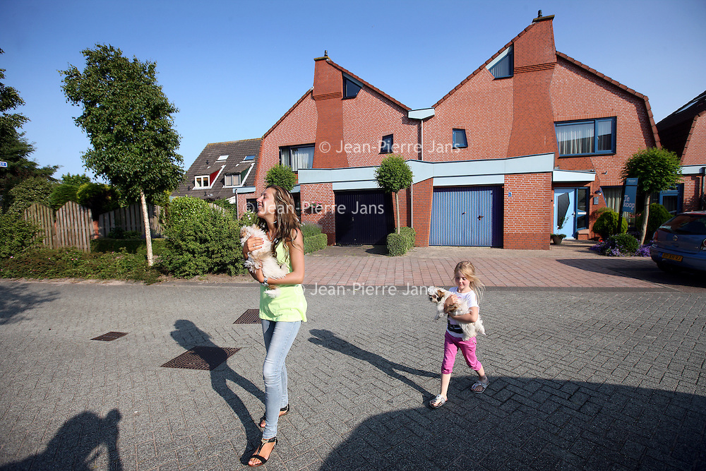 Nederland, Heemskerk , 5 juli 2013.<br /> In de wijk Waterakkers in Heemskerk heerst gedoe. Daar hebben een aantal bewoners tegen de regels in hun deuren een andere kleur geverfd, zoals bv op de foto. de blauwe garagedeur en kozijnen is toegestaan. De buurman heeft tegen de regels in zijn kozijnen en garagedeur zwart geverfd.