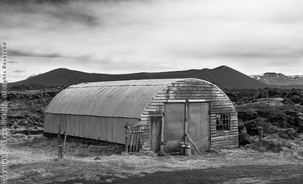 Barn with volcanic tephra ring in background, Lake Myvatn region, North Iceland