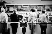Wachtende mensen bij een bushalte in Den Haag. Kind kijkt nieuwschierig rond, op de achtergrond een HTM  bus met Konmar (oude supermarkt keten) reclame