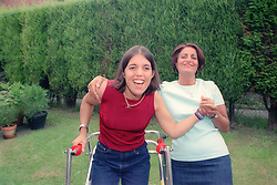 Girl with Cerebral Palsy using frame to walk; standing in garden with mother,