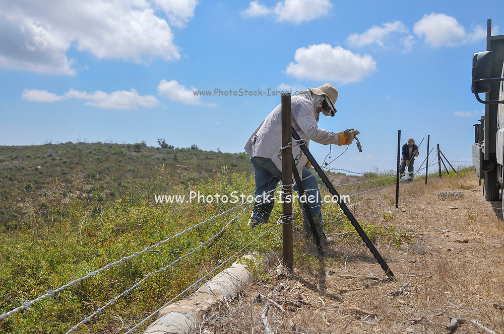 Farm workers fixing a fence around a field
