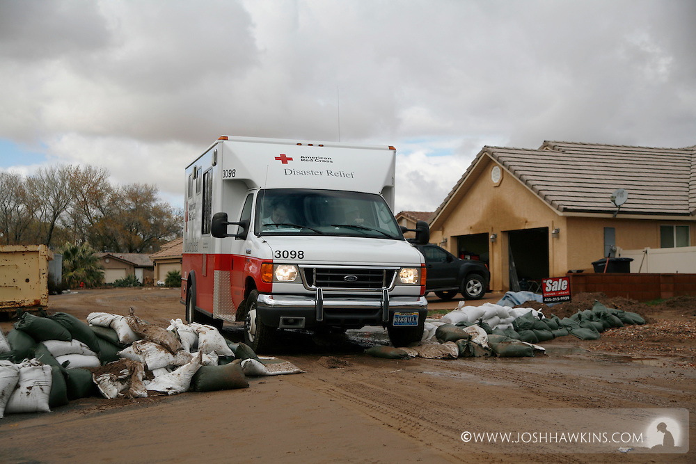 Red Cross disaster assessment teams in Beaver Dam, AZ on December 23rd, 2010 after the flooding the occurred over the previous days...The Emergency Response Vehicle goes over a former sandbag barricade on Beaver Dam Dr. while do disaster assessment.