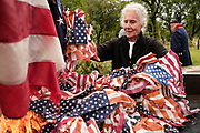 12 SEPTEMBER 2020 - DES MOINES, IOWA: KRISTINE BARTLEY throws US flags into the fire during a flag retirement ceremony at Glendale Cemetery in Des Moines. About 10 volunteers came to the cemetery Saturday morning to properly dispose of about 4,000 American flags. The flags had flown over veterans' graves, local businesses, and state offices. The US Flag Code calls for used American flags to be respectfully disposed of in a fire.    PHOTO BY JACK KURTZ