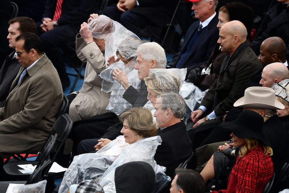 Former Presidents George W. Bush, Bill Clinton and Jimmy Carter cover up with raincoats during a brief rain at the 68th Presidential Inaugural ceremony on Capitol Hill January 20, 2017 in Washington, DC. Donald Trump was sworn-in as the 45th President.