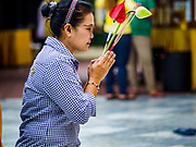 10 JULY 2018 - NAKHON PATHOM, THAILAND:  A woman prays at Phra Pathom Chedi in Nakhon Pathom. Nakhon Pathom is about 35 miles west of Bangkok. It is one of the oldest cities in Thailand, archeological evidence suggests there was a settlement on the site of present Nakhon Pathom in the 6th century CE, centuries before the Siamese empires existed. The city is widely considered the first Buddhist community in Thailand and the nearly 400 foot tall Phra Pathom Chedi is considered the first Buddhist temple in Thailand.    PHOTO BY JACK KURTZ