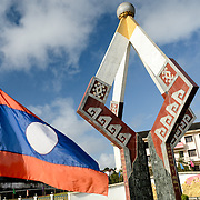The Independence Monument in Sam Neua (also spelled Samneua, Xamneua and Xam Neua) in northeastern Laos. In the foreground is a Lao national flag blowing in the wind.