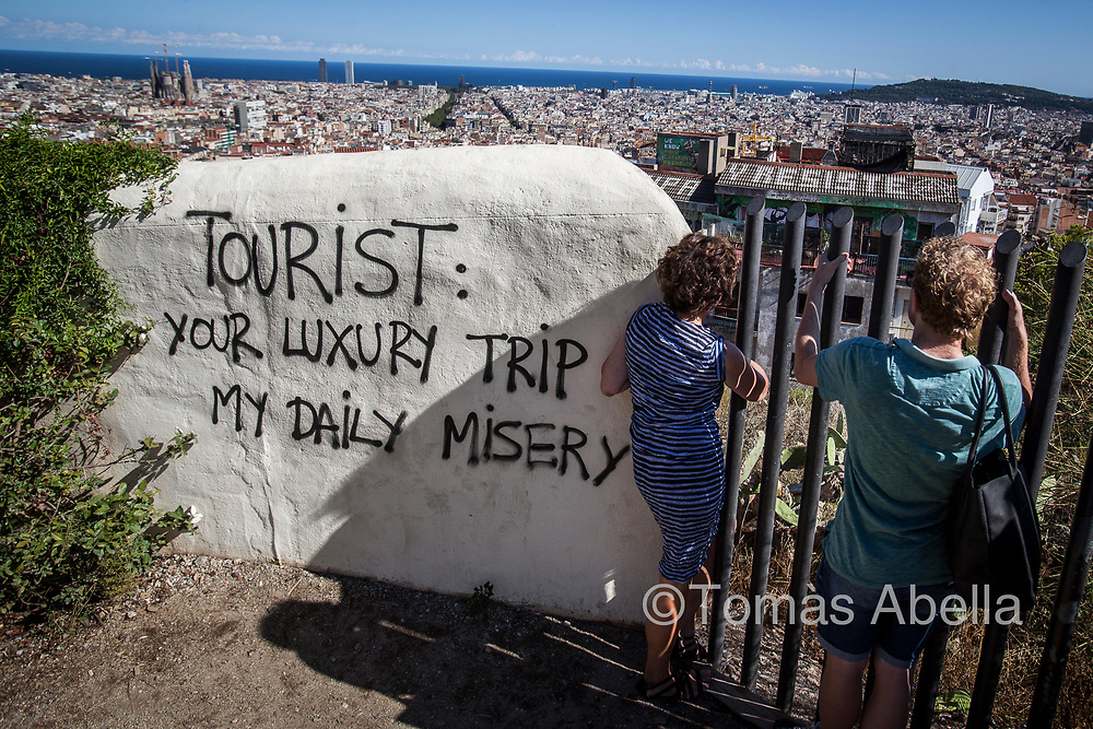 Tourists contemplating a panoramic view of the city from Park Güell. In the foreground of the picture, one of Barcelona's first squatted buildings, occupied in 1993 by the powerful movimiento social okupa, a social movement committed to pointing out the housing shortage in the city.