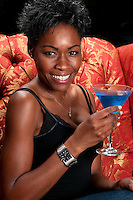 Young african american very happy having a blue martini cocktail in a restaurant.