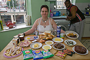 """Jill McTighe, a mother and school aide, with a day's worth of food on a bingeing day, in her kitchen in Willesden, northwest London, United Kingdom.  (From the book What I Eat: Around the World in 80 Diets.) The caloric value of her day's worth of food on a """"bingeing"""" day in the month of September was 12300 kcals. The calorie total is not a daily caloric average.  Jill is  31 years old; 5 feet, 5 inches tall;  and 230 pounds. Honest about her food addiction replacing a drug habit, Jill joked about being a chocoholic as she enthusiastically downed a piece of chocolate cake at the end of the photo session. Her weight has yo-yoed over the years and at the time of the picture she was near her heaviest; walking her children to school every day was the sole reason she didn't weigh more. She says this photo experience was a catalyst for beginning a healthier diet for herself and her family. """"Do I cook? Yes, but not cakes. I roast. Nothing ever, ever is fat-fried!"""" MODEL RELEASED. [Use of Jill McTighe images must be used contextually only and use cleared with Peter Menzel Photography on a case by case basis.]"""