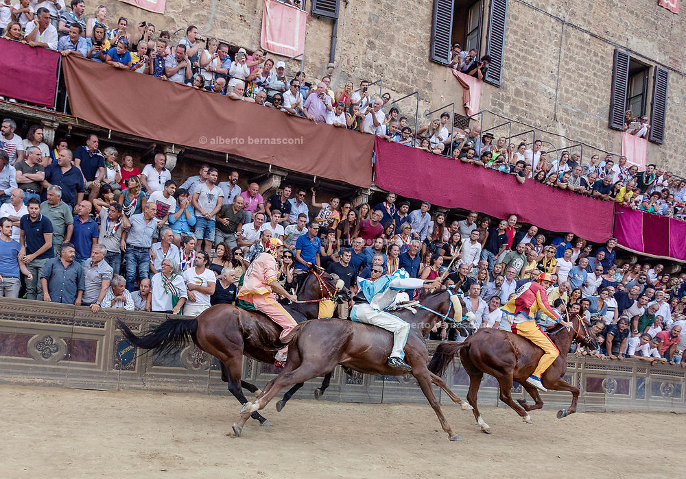 Italy, Siena, the Palio:  Onda pssing MOntone , Chiocciola still heading. the straight section between the Curva del Casato heading to the arrival At the shot of the mortaretto, the horses come out of the Entrone and line up at the starting line, known as the mossa. As soon as the last horse reaches the starting line the race begins and lasts for three rounds of the square (about 1 kilometre in total). The first horse to cross the finishing line is the winner, regardless of whether it is still mounted.