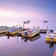 A group of small aluminum rental boats at a dock at sunrise. Damariscotta Lake. Jefferson, Maine