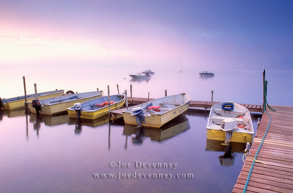 A group of small aluminum rental boats at a dock at sunrise. Damariscotta Lake. Jefferson, Maine