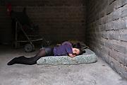 Leonela (10) sobre el colchón que comparte con su madre Anita (25) para dormir. La habitación que alquilan para vivir tiene aproximadamente 3 x 3 metros. Leonela tiene una parálisis cerebral severa con compromiso del sistema nervioso central.