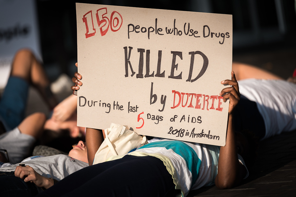 26 July 2018, Amsterdam, the Netherlands: At a die-in demonstration by the entrance of the 2018 International AIDS Conference, a woman holds a sign criticizing the war on drug users being conducted by Philippines President Rodrigo Duterte.