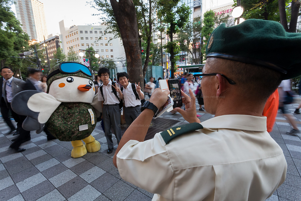 A soldier takes a photo of two junior high-school boys with Touchi, a mascot for the Tokyo area Japanese Self Defence Force (JSDF) as he greats pedestrians in Ikebukuro, Tokyo, Japan Friday September 29th 2017. The Ministry of Defence, each Autumn starts a recruitment drive to encourage more young people to join the Japanese Self Defence Force. Military service in Japan is neither compulsory nor popular and with regional tensions increasing and Hawkish politicians in power they are gain to raise the number of military personnel available.