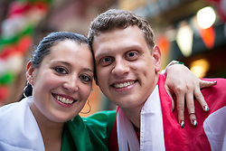 © Licensed to London News Pictures . 14/06/2014 .  Manchester , UK . L-R Italy fan Paola Gigiello (29) and England fan James Price (27) who are girlfriend and boyfriend , about to watch the match at a branch of Walkabout in Manchester . If Italy wins Paola gets to fly the Italian flag from the window of their flat in the . Football fans in Manchester City Centre this evening (Saturday 14th June 2014) as England prepare to play Italy in their first match of the 2014 World Cup , in Brazil . Photo credit : Joel Goodman/LNP