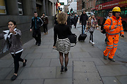 City worker with her own unique style walks down Bishopsgate in the City of London, England, UK. Wearing a black and white striped dress this woman also has carefully tended hair which makes her stand out from the crowd.