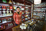 Woman working in tea shop near the Yu Garden Bazaar Market, Shanghai, China