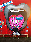 Man drinking under a mouth painting in the Shangri La field, Glastonbury Festival 2016. The Glastonbury Festival is the largest greenfield festival in the world, and is now attended by around 175,000 people. Its a five-day music festival that takes place near Pilton, Somerset, United Kingdom. In addition to contemporary music, the festival hosts dance, comedy, theatre, circus, cabaret, and other arts. Held at Worthy Farm in Pilton, leading pop and rock artists have headlined, alongside thousands of others appearing on smaller stages and performance areas.