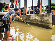 22 SEPTEMBER 2016 - BANGKOK, THAILAND:  A woman does subsistence fishing in khlong (canal) next to the Wat Dhevaraj Kunchon community. The community near Wat Dhevaraj Kunchon, which is on the Bangkok riverfront, is facing eviction because the city wants to build a promenade to attract tourists and high end shopping.       PHOTO BY JACK KURTZ