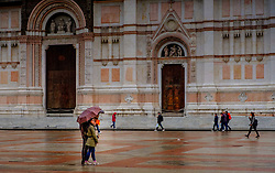 People walking in the rain in the early evening outside the Basilica di San Petronio, Bologna, Italy<br /> <br /> (c) Andrew Wilson   Edinburgh Elite media