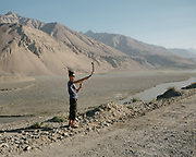 Tourist doing selfie with selfie stick with Afghanistan in the background. <br /> Trekking between Yamchun village and Darshai. Sights and places to see while walking along the Tajikistan side of the Wakhan Corridor.