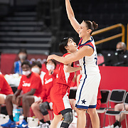 TOKYO, JAPAN August 8:  A smiling Diana Taurasi #12 of the United States holds the ball aloft and passes the ball as Nako Motohashi #15 of Japan defends during the Japan V USA basketball final for women at the Saitama Super Arena during the Tokyo 2020 Summer Olympic Games on August 8, 2021 in Tokyo, Japan. (Photo by Tim Clayton/Corbis via Getty Images)