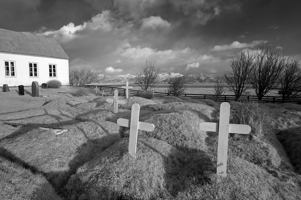 Infrared photo - An old church with grave sites marked by wooden crosses in southeast Iceland. Photo/Andrew Shurtleff Photography, LLC