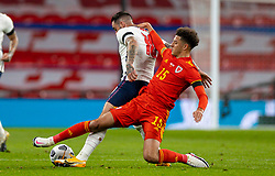 LONDON, ENGLAND - Thursday, October 8, 2020: Wales' Ethan Ampadu (R) tackles England's Danny Ings during the International Friendly match between England and Wales at Wembley Stadium. The game was played behind closed doors due to the UK Government's social distancing laws prohibiting supporters from attending events inside stadiums as a result of the Coronavirus Pandemic. England won 3-0. (Pic by David Rawcliffe/Propaganda)