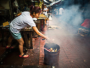 "28 AUGUST 2015 - BANGKOK, THAILAND:  A woman burns ""ghost money"" for her ancestors on Hungry Ghost Day in Bangkok's Chinatown. Mahayana  Buddhists believe that the gates of hell are opened on the full moon of the seventh lunar month of the Chinese calendar, and the spirits of hungry ghosts allowed to roam the earth. These ghosts need food and merit to find their way back to their own. People help by offering food, paper money, candles and flowers, making merit of their own in the process. Hungry Ghost Day is observed in communities with a large ethnic Chinese population, like Bangkok's Chinatown.       PHOTO BY JACK KURTZ"