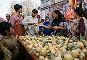 Women buying fruit from street seller in Old Delhi, India